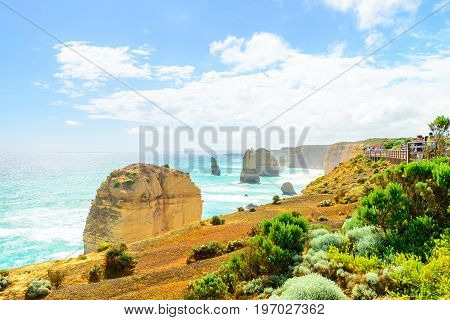 Port Campbell Victoria Australia - December 30 2016: People walking along the Castle Rock pathway and enjoyong the view of Twelve Apostles on a bright day
