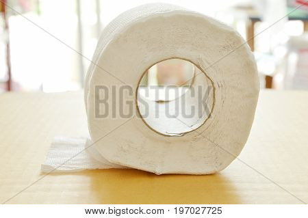 white tissue paper rolling on brown hard sheet board