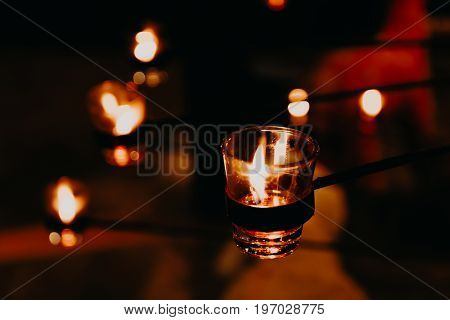 Candles light background and wallpaper. Christmas candles burning at night. candle flames glowing in the dark.