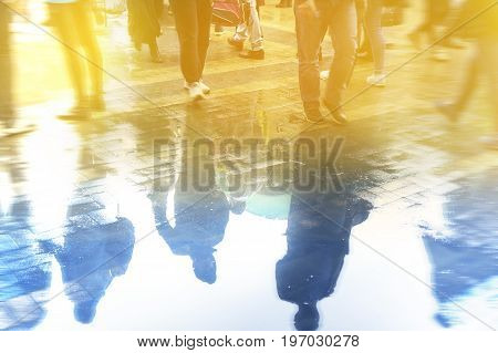 People go to work reflected in a puddle