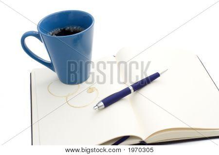 Coffe Mug On Notebook