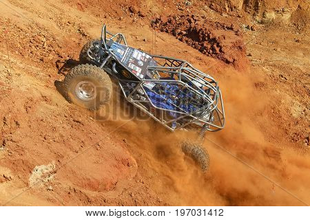 Blue Car Powering Up Steep Hill, Kicking Up Sand And Dust.