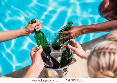 Cropped Image Of Human Hands Taking Cold Beer From Ice Bucket Standing On Edge Of Swimming Pool