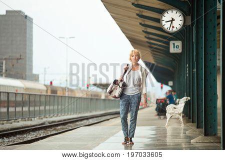 Blonde caucasian woman waiting at platform of railway station bearing vintage shoulder bag.