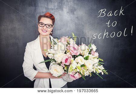 Happy Teacher With Flowers On Blackboard Background
