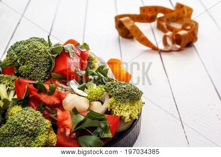 Salad of tomato, carrots, broccoli, garlic, onion and greens in a black plate on white boards a centimeter for waist measurement