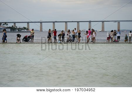 Rio de Janeiro Brazil - may 01 2017: Cariocas and tourists enjoy the holiday strolling along the waterfront. In the background the Rio-Niter