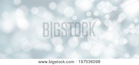 Abstract silver bokeh background with snowfall at wintertime