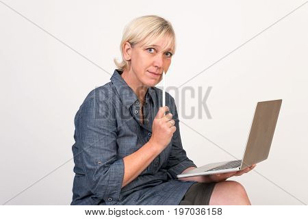 beautiful european mid aged woman working at a laptop thoughtful - studio shot in front of light background