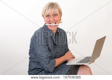 beautiful european mid aged woman working at a laptop biting on pencil - studio shot in front of light background