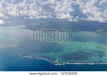 Aerial picture of the southeast south east coast of Mauritius Island. Beautiful lagoon and reef barrier of Mauritius Island shot from above. Fouquets Island with a lighthouse in the foreground.