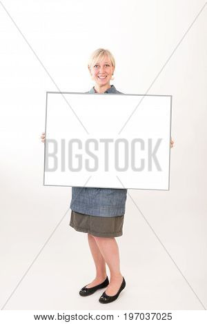 beautiful european mid aged woman in business dress holding a blank white board - studio shot in front of light background