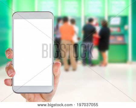 Woman's hand holding smart phone with white screen display with blur people using ATM background.