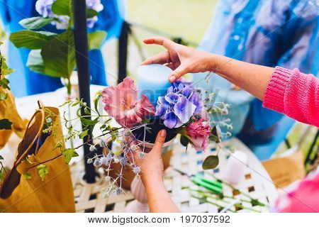 Florist at work, making a flower composition. Wedding details. Woman collecting a composition of different, colorful flowers and a blue candle. Close-up, outdoors