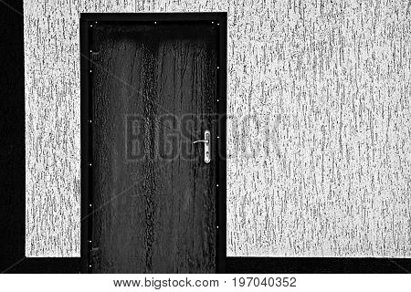 Black closed door on the wall of a gray private house