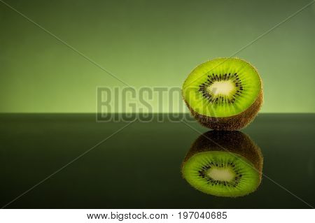 Isolated fresh and juicy green kiwi fruit on green light background healthy food concept