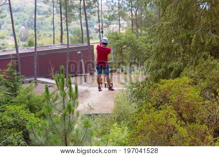 MEZIO, PORTUGAL - JULY 22, 2017: young adventurous man doing a slide in zip lining thru the forest. July 22, 2017, Mezio, Portugal.