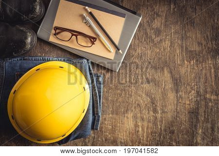 Equipment works on old wooden floor top view,Yellow helmet Safety shoes glasses notebooks pens pencils on old wooden boards
