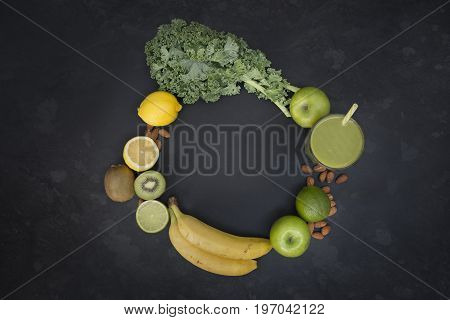 Healthy living concept with a glass of green smoothie surrounded fruit and vegetables in a circle shape with room for text.