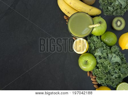Healthy living concept with a glass of green smoothie with fruit and vegetables including Kale and citrus fruits.