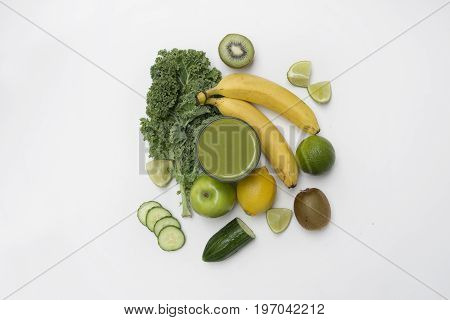 Top down view of healthy lifestyle green smoothie made with fruit and vegetables on a white background. Lifestyle concept.