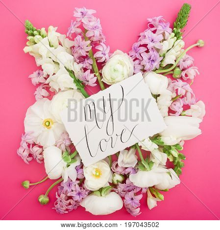 Composition with paper card and flowers on pink background. Quote on card