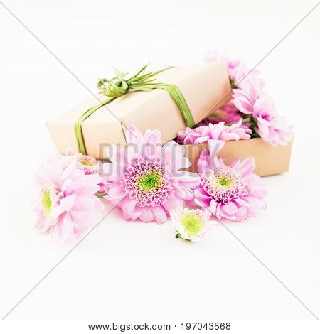Paper gift box and pink flower on white background. Flat lay, top view.
