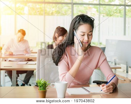 Young businesswoman talking on smartphone and using writing on notebook, concept for receipt order or consumer support