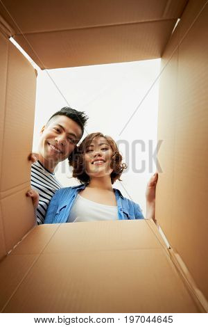 Cheerful Vietnamese couple opening cardboard box and looking inside, group portrait
