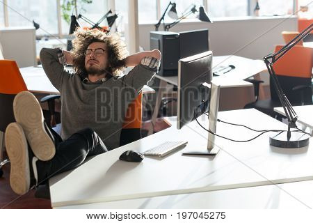 Full length of a relaxed casual young businessman sitting with legs on desk at office