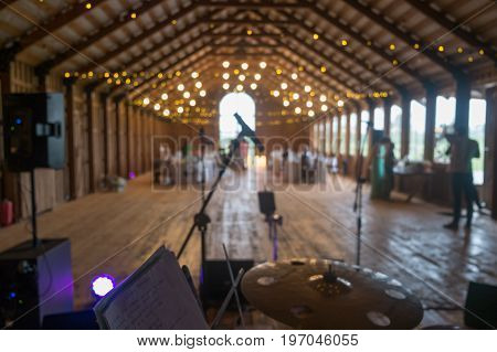 View from drum set on a stage with focus on microphone. Wedding in an old farm loft.