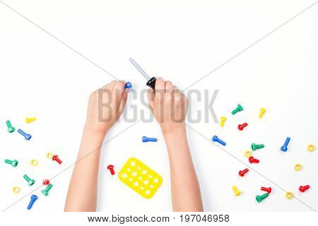Top view on child's hands playing with colorful toys tools on the white table background.