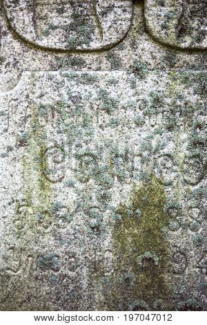 Stony surface of the old gravestone with Cyrillic inscriptions
