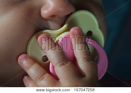 The baby is holding a rubber nipple in her mouth. Macro