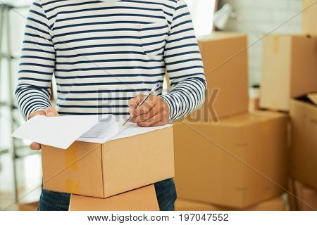 Close-up of unrecognizable man signing documents for moving, pile of cardboard boxes on background