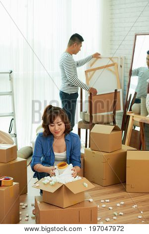 Loving Asian couple gathered together in living room of new apartment and unpacking  cardboard boxes with stuff
