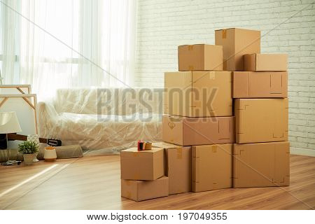 Interior of empty living room of new apartment with pile of moving boxes, personal belongings and sofa wrapped in plastic