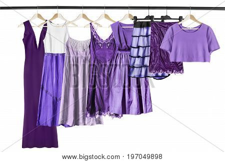 Set of purple woman clothes on clothes racks isolated over white
