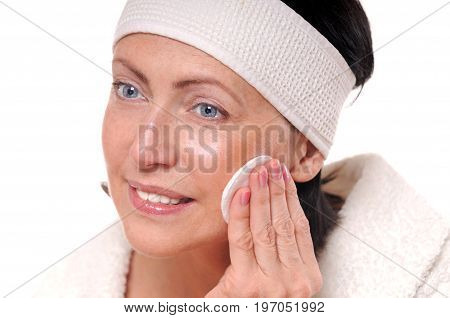 Portrait Of Pretty Senior Woman Taking Off Makeup