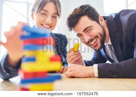 Business colleagues in team building workshop building blocks