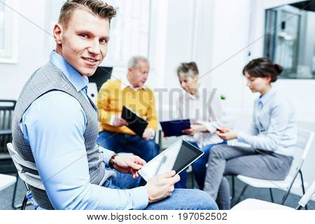 Man as consultant with tablet computer in business consulting workshop