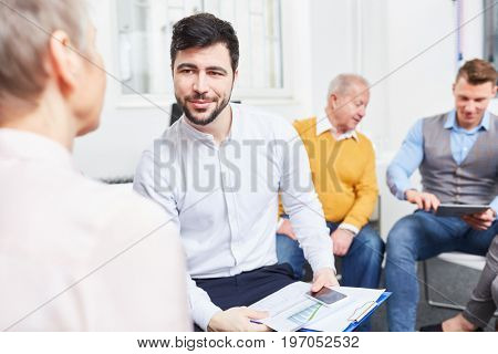Man as business consultant in team meeting chats with senior woman
