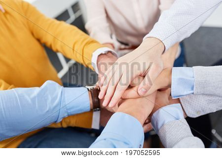 Team stack hands together for team building exercise