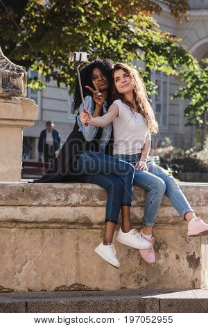 Two attractive young girls making selfie near the monument in the downtown. One girl is black.