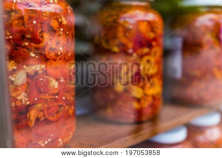 Marinated Red And Yellow Peppers In Large Jars On Display Behind Glass Window With Pizza Sign