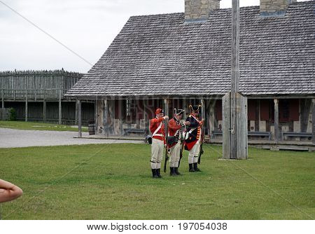 MACKINAW CITY, MICHIGAN / UNITED STATES - JUNE 18, 2017: Costumed interpreters, on the parade ground of Fort Michilimackinac, in the Colonial Michilimackinac State Park, demonstrate the use of muskets.