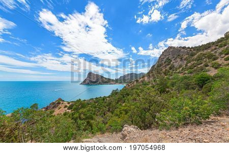 View of the Bay to the resort village near the mountains and with a large headland in the sea. Cape Chyken Peninsula of Crimea resort Noviy Svet