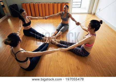 Multi-ethnic group of cheerful women sitting in circle and holding hands while doing stretching exercise, interior of modern fitness studio on background