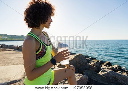 Young fitness woman resting after jogging and holding water bottle outdoors