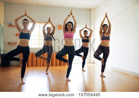 Group portrait of cheerful sporty women standing in tree pose while practicing yoga in spacious fitness studio